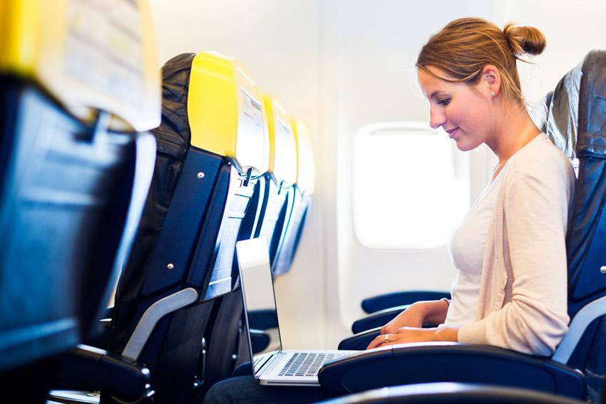 Chica con un aparato electrónico encendido, una de las cosas que no debes hacer en un avión