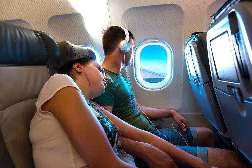 Chica ocupando dos asientos, una de las cosas que no debes hacer en un avión
